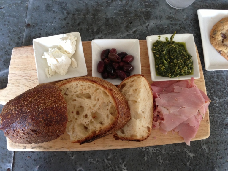 French Picnic: rosemary ham, whipped goat cheese, kalamata olives, fresh made pesto and hot Italian bread.