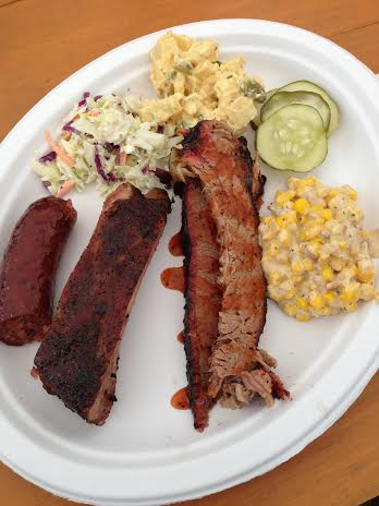 The whole plate: sausage, pork ribs, brisket with sauce, creamed corn, homemade pickles, potato salad and blue cheese cole slaw